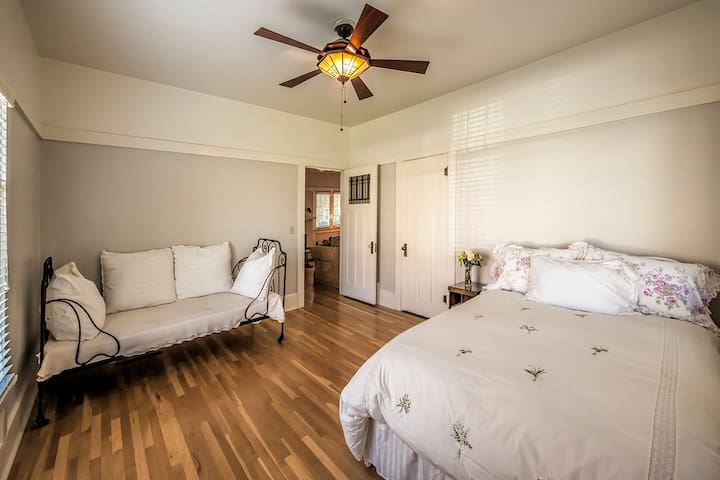 Main floor bedroom is spacious with additional cozy seating.