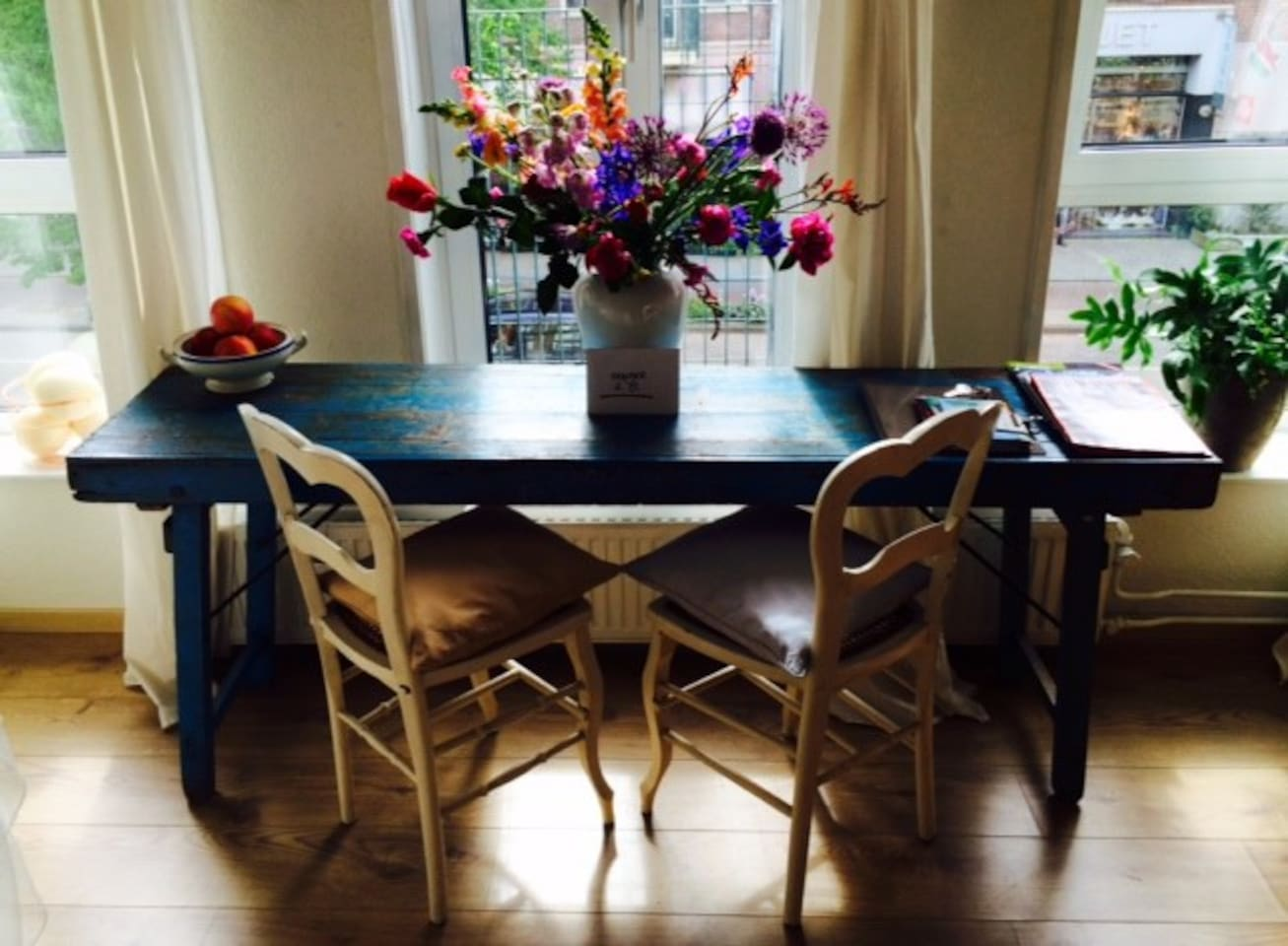 The large table for two in front of an opening balcony door; to eat, work, read, write, relax