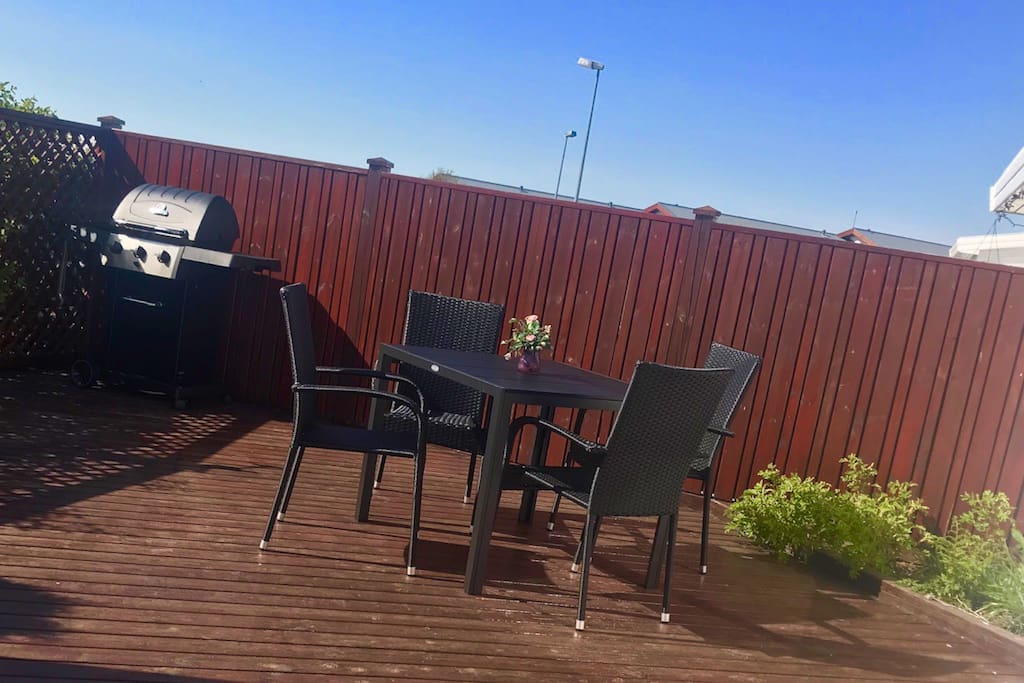 A Patio with gas grill, table and chairs