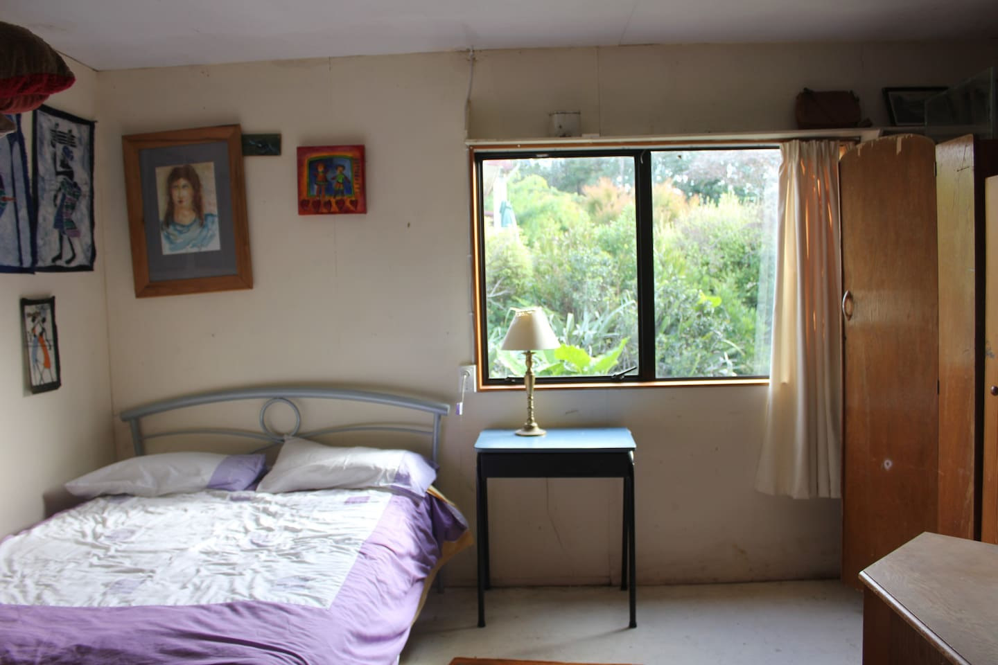 Queen bed in private space separated from dormitory and living area by cupboards