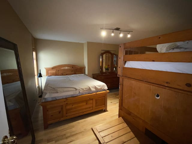 Downstairs queen bedroom with quiet room and separate upper bunk. Lots of storage in the bunkbed and in the dresser for longer-term stays also