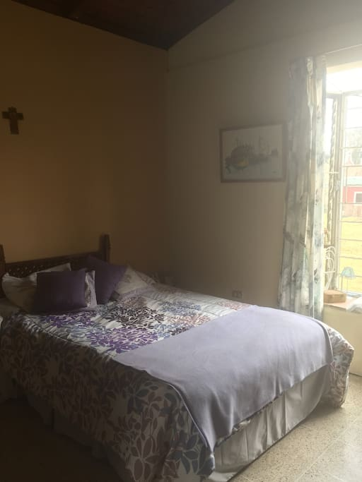 Habitación, cama matrimonial, vista al jardín.