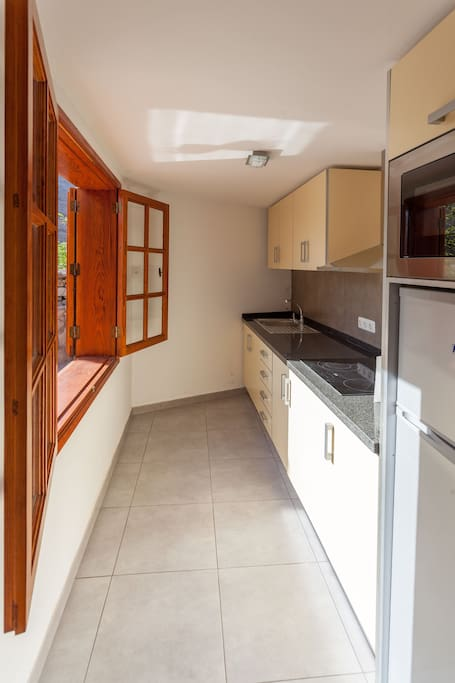 Kitchen with window to the terrace and barbecue area.