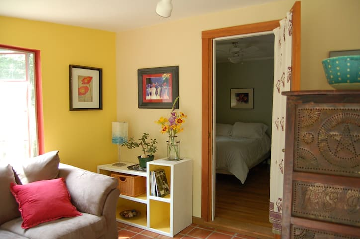 The sunporch is bright and cheery with yellow end walls and lots of beautiful art.