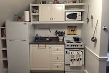 Cute kitchen with everything you need to whip up a meal! Roll out cart provides extra workspace and pantry.