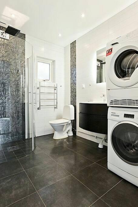 Fin badrum med tvättmaskin och torktumlare