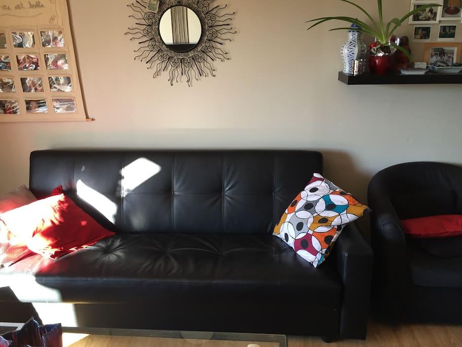 Canapé 3 places convertible avec 1 club dans le salon face à la TV