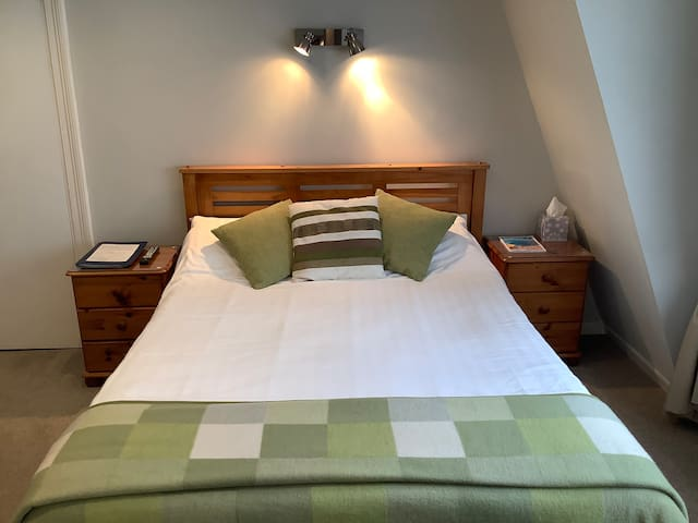 Double bed with over head lighting and bedside cabinets.
