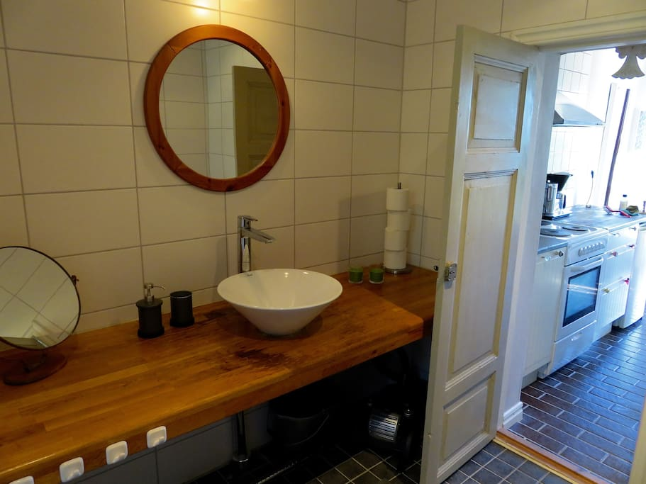 Kaklat badrum med dusch, tvättmaskin, WC