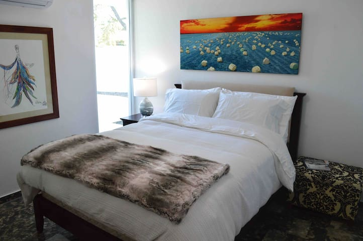 Guest room four with queen bed and private pool access.