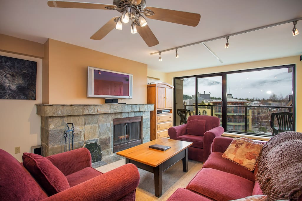 The living room features a stunning stone wood burning fireplace.