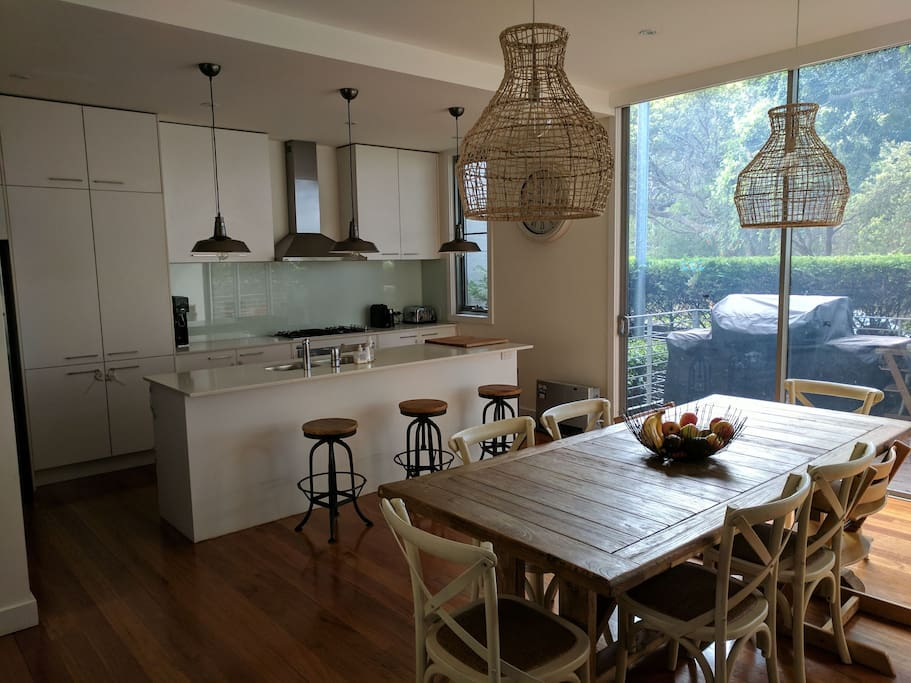 Open plan kitchen and dining with 5 burner gas BBQ on front deck overlooking Easton Park