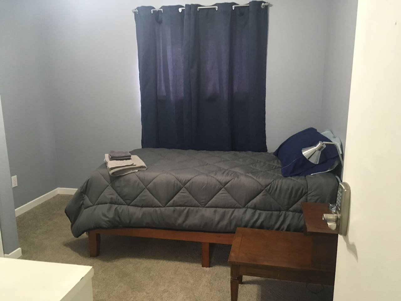 Single bed, dresser, nightstand, lamp, with ceiling fan.