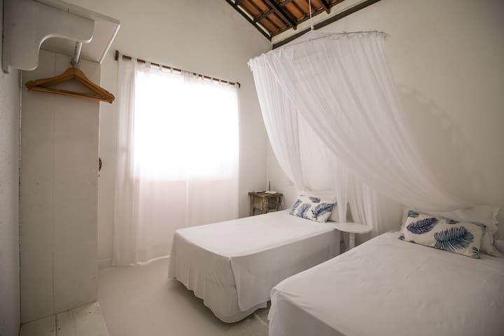 Quarto 1 com mosqueteiro, ar condicionado e roupeiro. Pode ser equipado com duas camas de solteiro ou cama casal tamanho queen size.