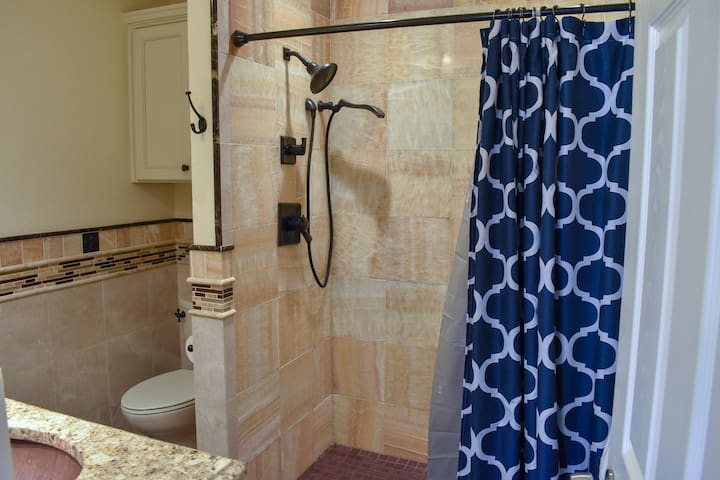 Bathroom equipped with stand-up shower that is all marble with oil-rubbed bronze fixtures
