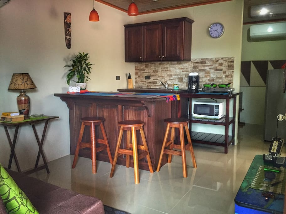 Fully equipped kitchen along with a wood counter top and a nice living room.
