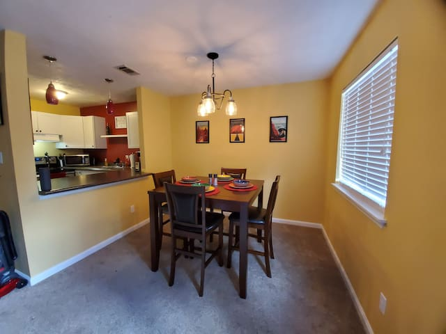 Dining room and fully stocked kitchen with Keurig coffee maker and dishwasher.