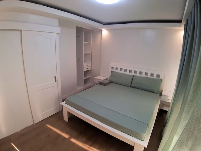 Master bedroom with a king size bed, built in cabinet and a working table. It has access to the balcony
