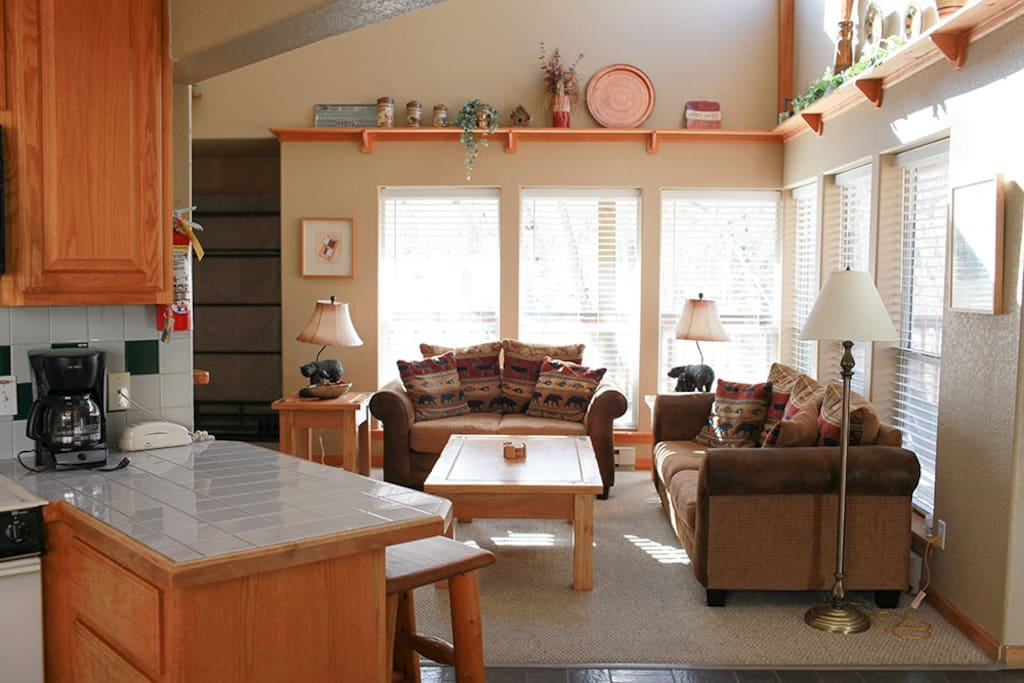 Relax in the spacious living room with vaulted ceilings, large windows, fireplace and TV.
