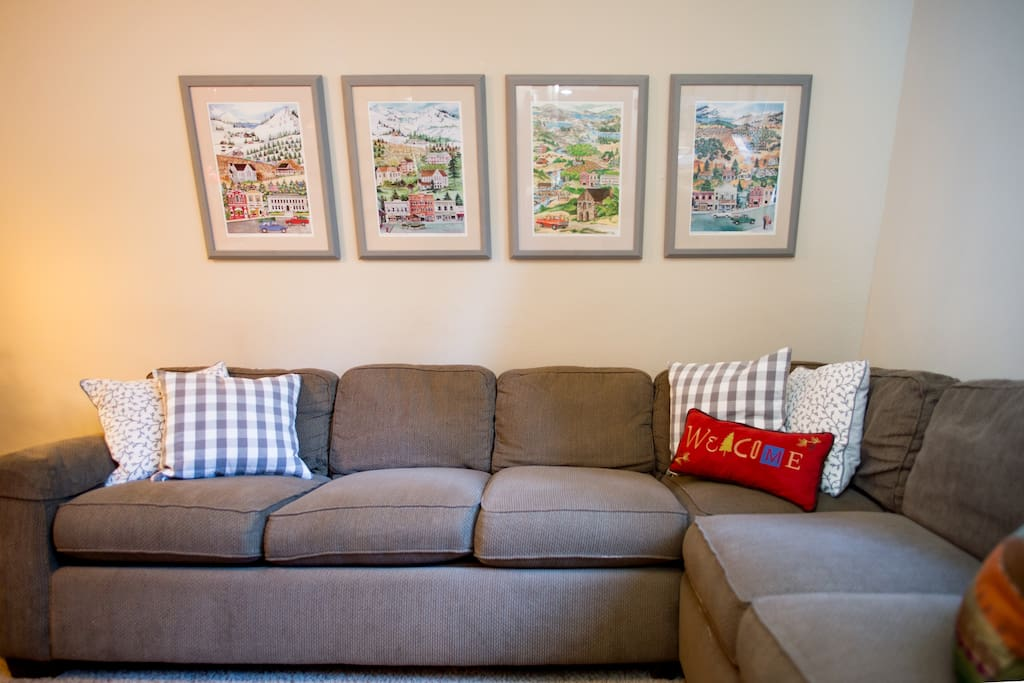 Local artwork displayed on the wall behind the large sectional couch that can sleep two.