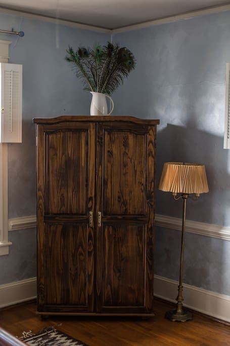 A large bureau and closet provide plenty of storage for guests to store belongings.