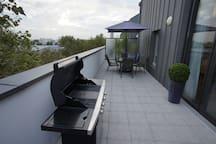 La terrasse côté cuisine, avec une fenêtre qui communique et le grand barbecue gaz au premier plan.