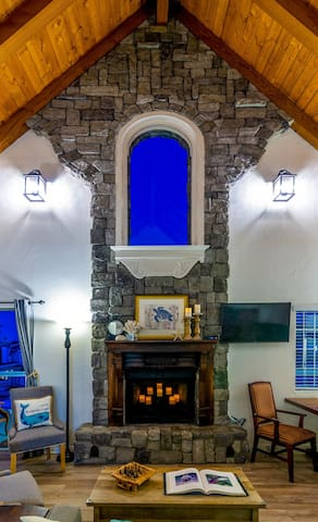 Custom stonework fireplace with European accents and dramatic vaulted shiplap ceiling. Wall mounted smart TV.