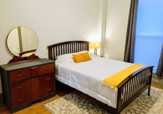 The guest room features a comfortable queen bed, dresser, bedside table, work desk, a couple of lamps, and a closet to hang clothes in/stow bags.