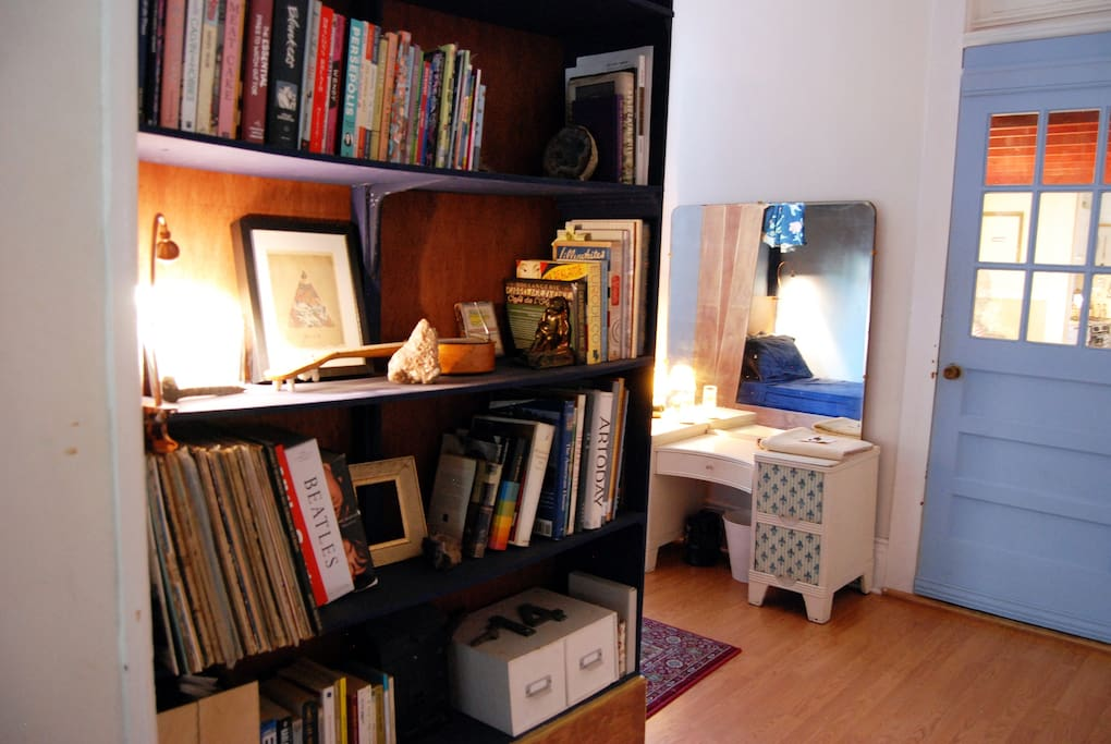 Bookshelf at the end of the bed,  your vanity, and door to our loft room for rent