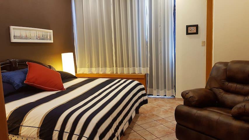 Amplia recamara con cama kingsize, sillón reclinable, área de trabajo con suficiente luz natural.