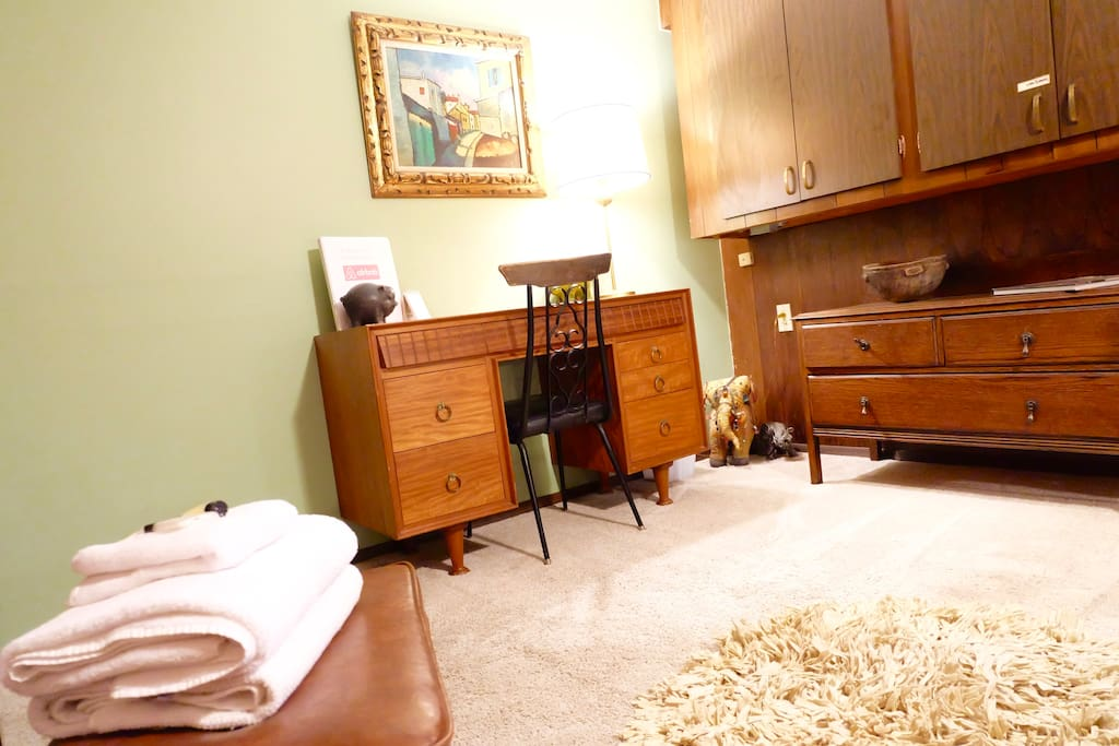 Large carpeted room has a vintage desk and chair, small dresser and shelving unit for storage.