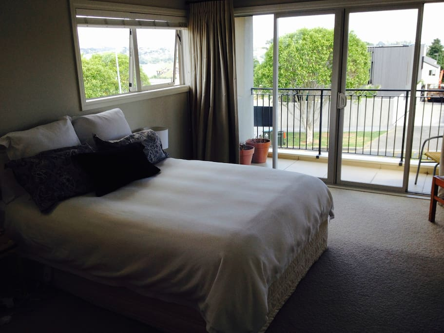 The spacious bedroom has lovely views over the water to the harbour and Cornwall Park.