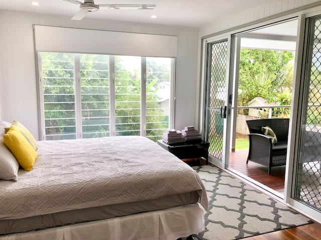 The master bedroom has a luxurious king-sized bed, ensuite bathroom, TV and direct balcony access.