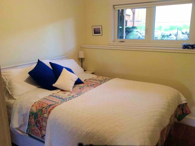 Lovely queen bedroom with cute end tables, lamps, and large new casement window