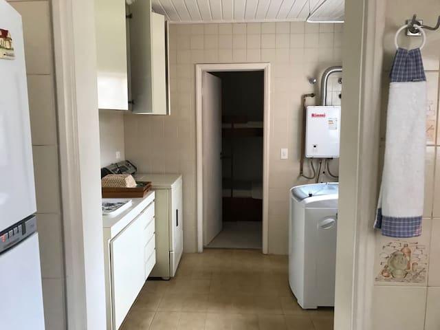 Lavanderia com máquina de lavar e secadora, quarto com beliche ao fundo.