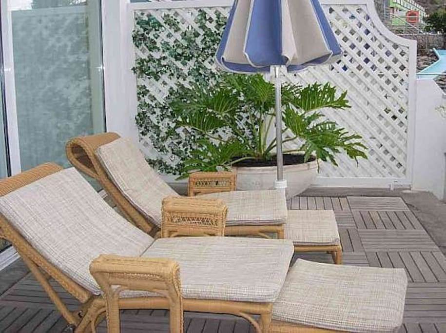 two sunbeds on terrace and table with 4 chairs