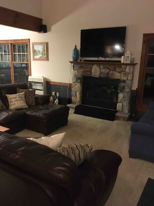 Comfortable Living room with large seating areas, HDTV with surround sound, and wood burning fireplace.