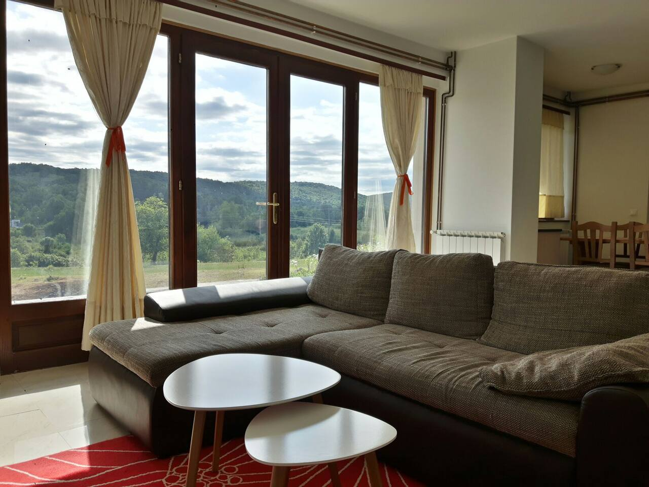Sofa with coffee table, and beautiful view throught the glass.