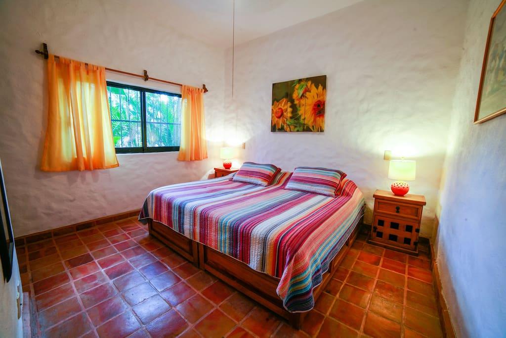 King-sized bed in Sunflower Suite's bedroom - overlooking the front patio garden.