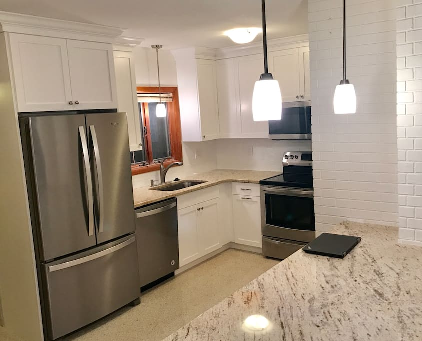 Remodeled kitchen with Shaker style wood cabinets, stainless steel appliances and granite counters