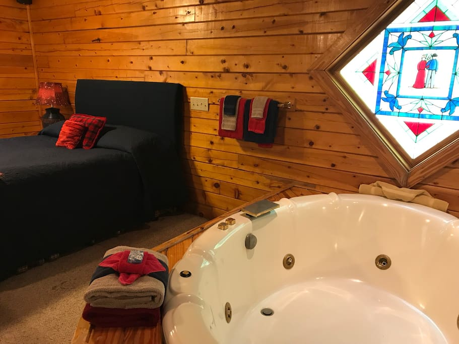 Cabin 1, Rustic Romance has a queen bed, Jacuzzi for two set off with a stained glass window