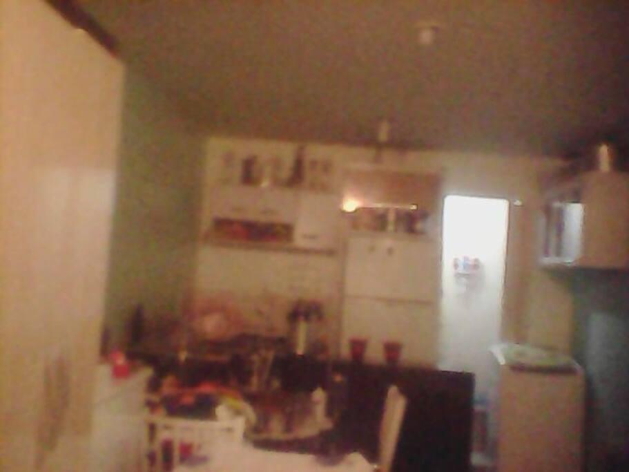 cozinha americana com fogão geladeira duplex armários e porta do banheiro