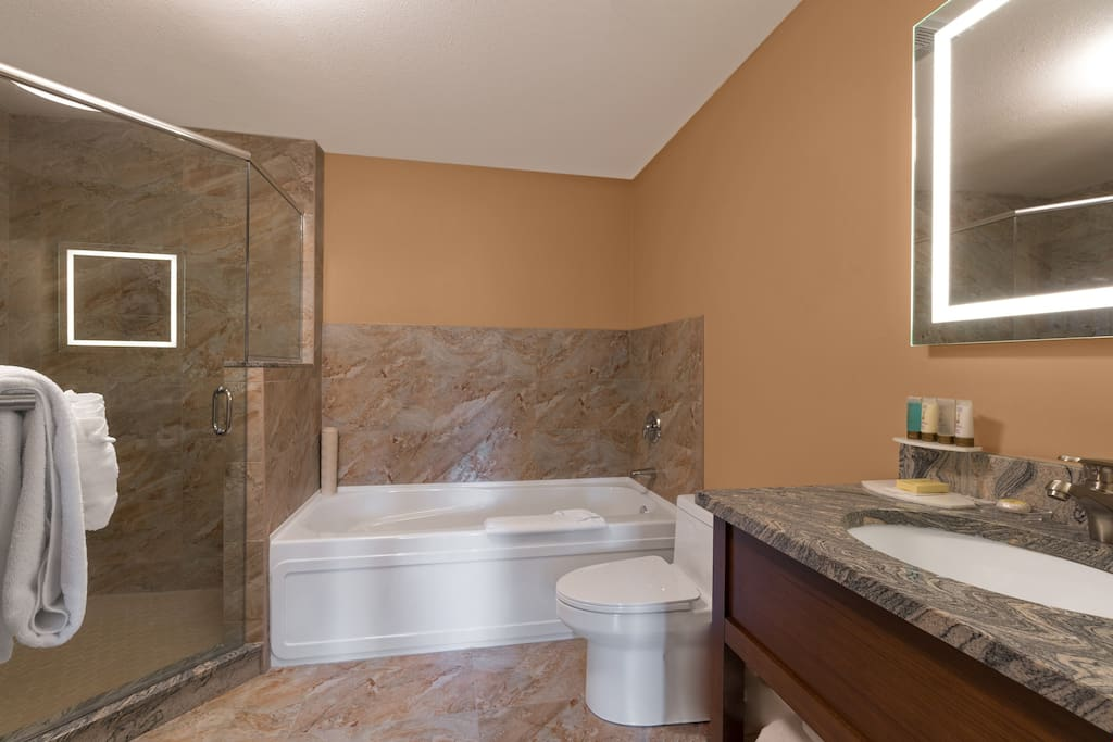 The spacious bathroom is pristine and clean.