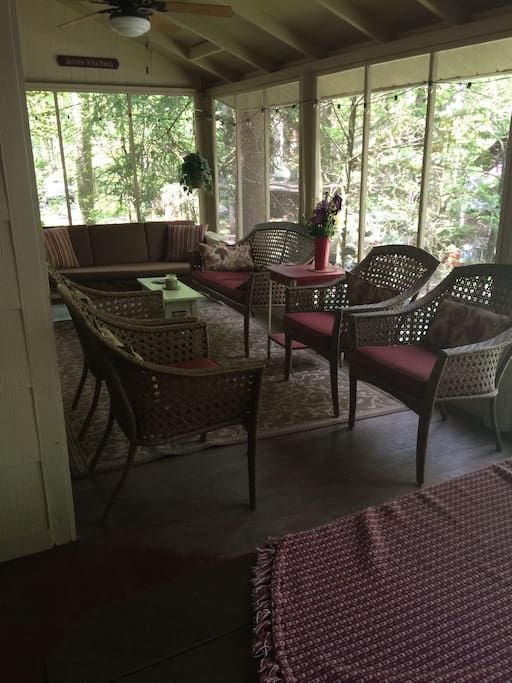 Screened in porch with table and sitting area