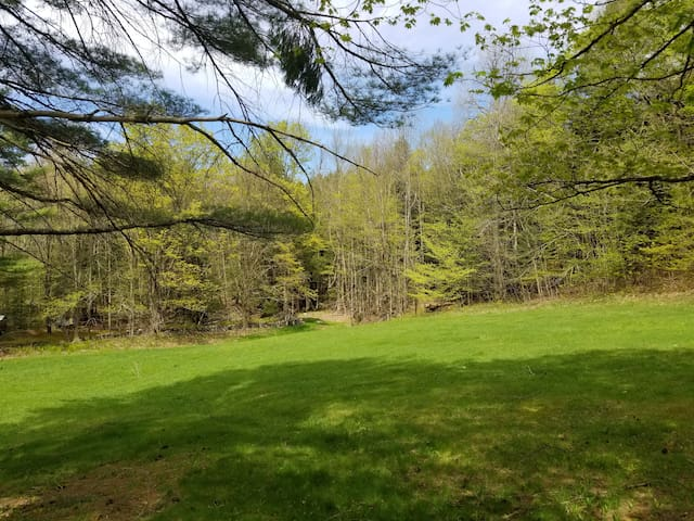 Summer view from The Loft across the rolling green to the on-property brook and waterfall. Hiking available right off the property.