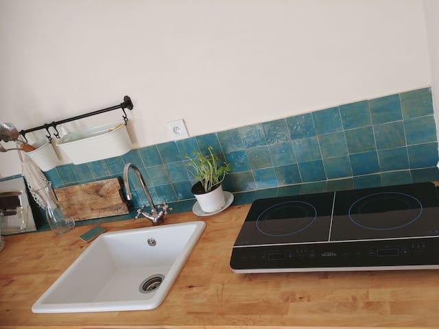 La cuisine avec plaques à induction, réfrigérateur et congélateur, lave vaisselle, théière, machine à café filtre.