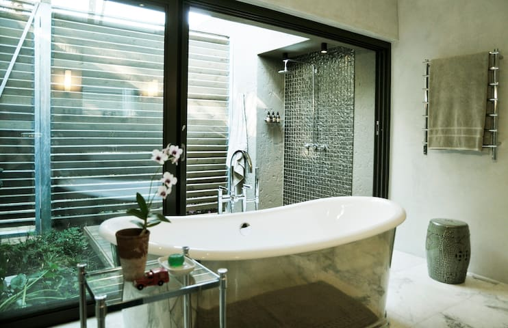 Luxurious bathroom featuring a freestanding pewter bath and an outside shower within an enclosed tropical courtyard.