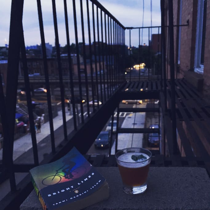 Relax on the fire escape with sunset views, cocktail and a book