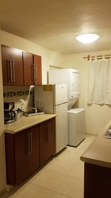 Kitchen with coffee pot, full refrigerator, washer,  dryer