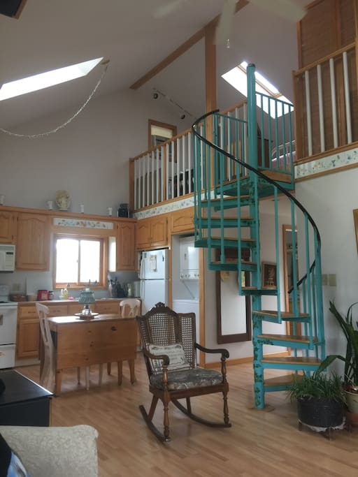 View of kitchen and spiral staircase to loft from living room.